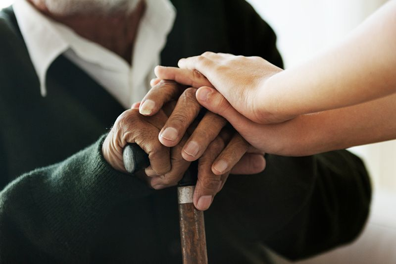 closeup of young person's hands over elderly person's hands