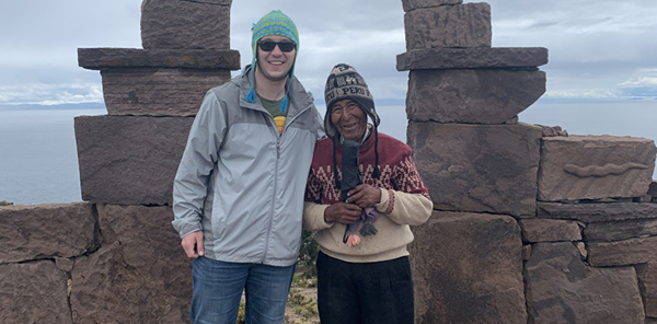 students poses with Peruvian man