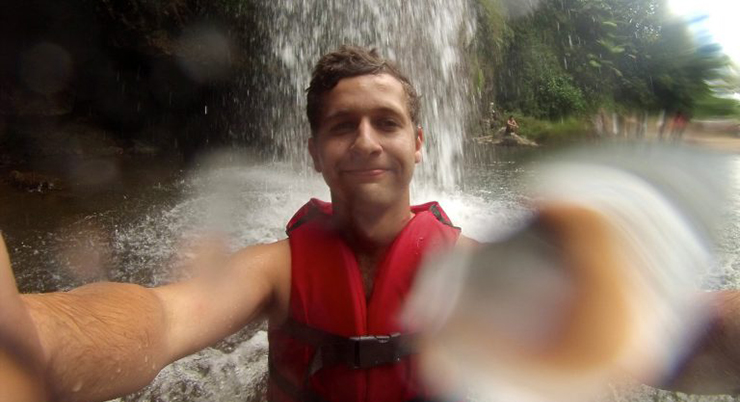 Male student takes selfie under waterfall