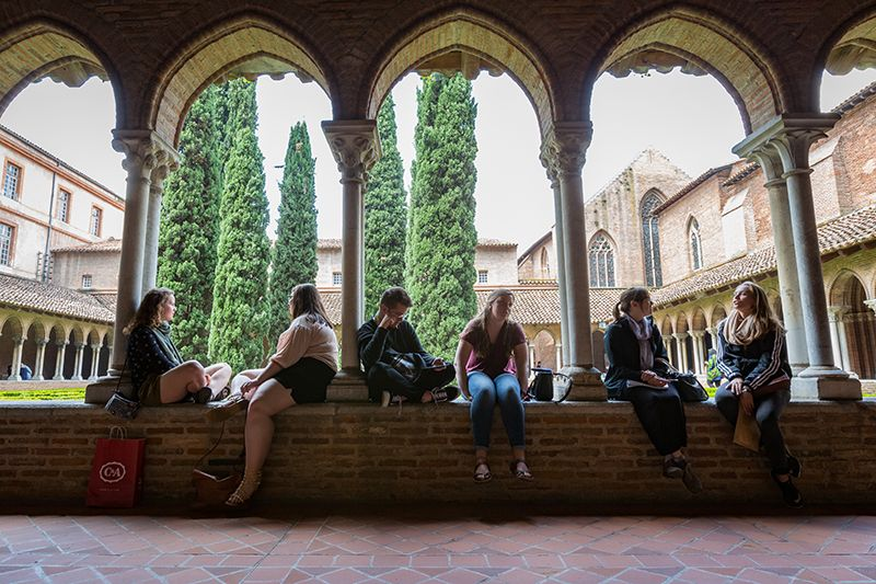 Students relax in a quiet cloister in Toulouse, France.