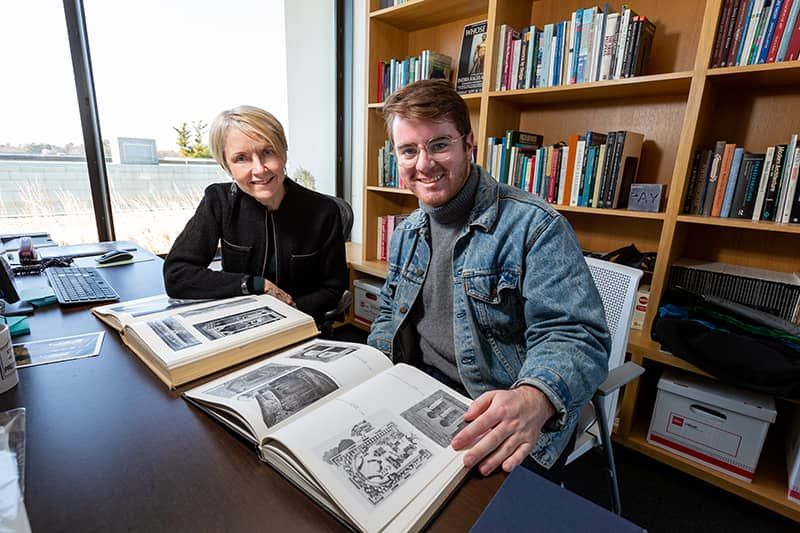 Professor and student examine art history volume in book-lined office