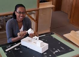 Female architecture student is in studio. Model in front of her.