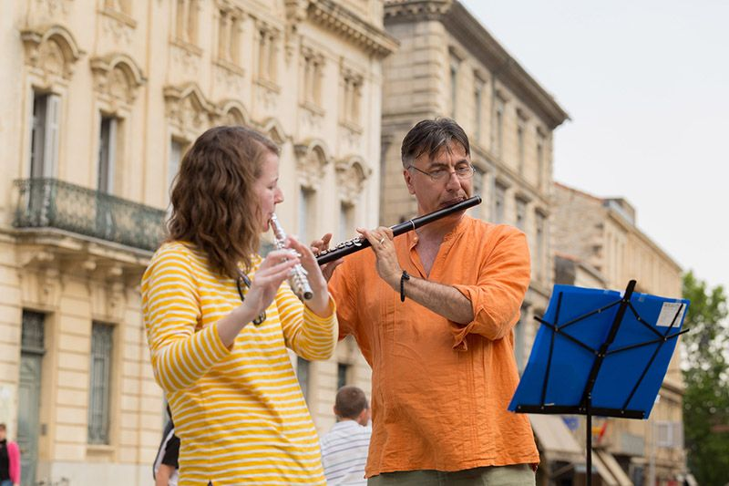Two flute players perform in a European town square.