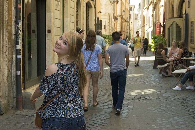 Group of students walk on street in Rome.