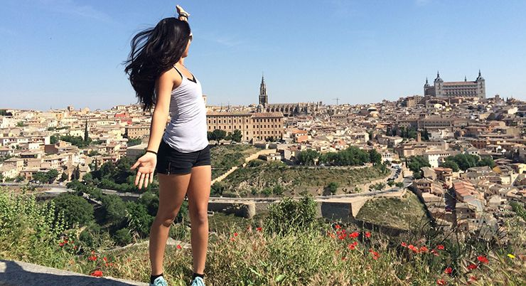 Young woman on hilltop gestures back towards European city.