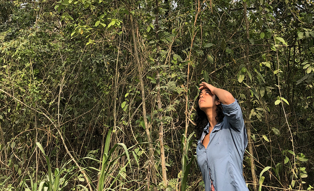 Female student shields eyes from sun in jungle