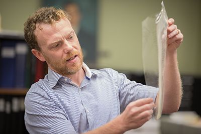 Man pulls manuscript folio from protective cover