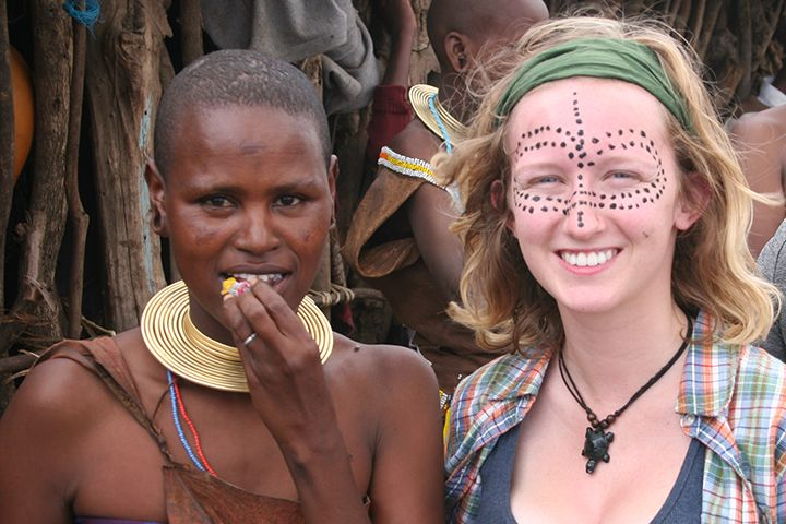A female student with face painted poses beside a Tanzanian woman.
