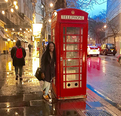 Woman leaning against red telephone booth