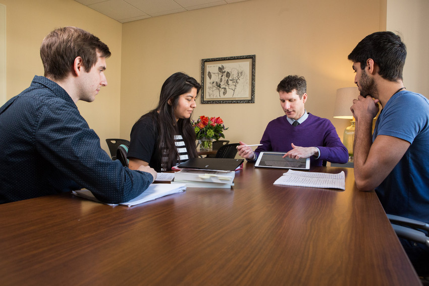 four people sit around a table talking