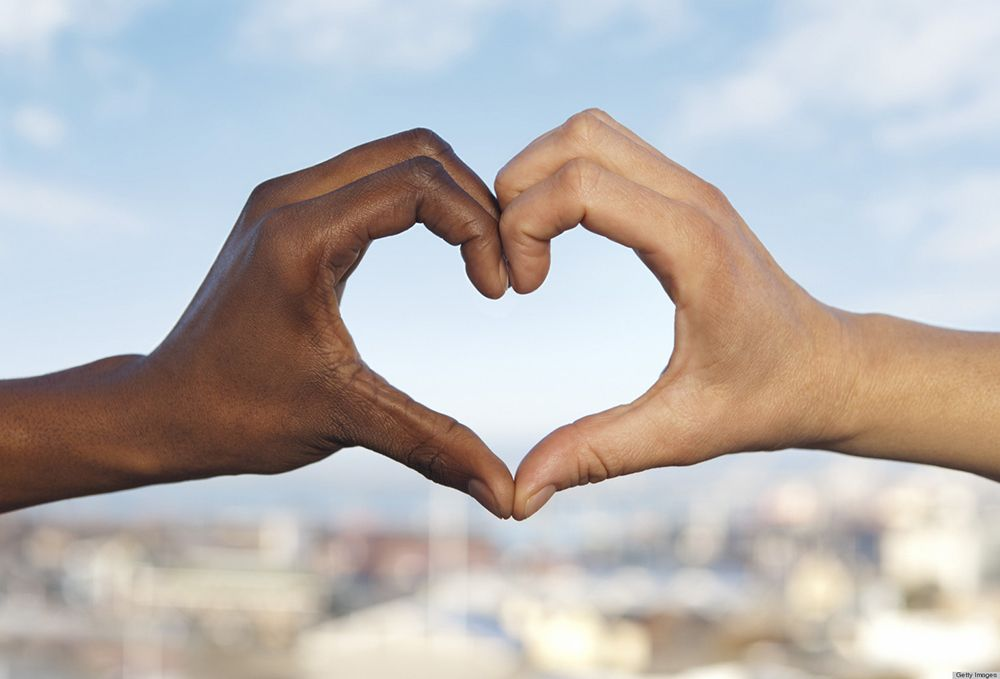 Two hands, of different races, form a heart.