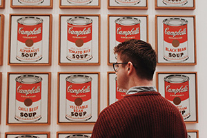 student standing in front of Warhol painting
