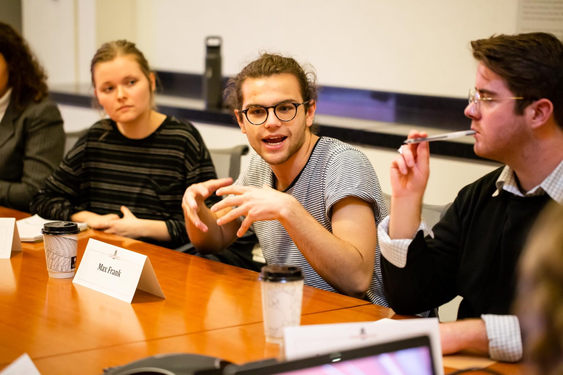 male student speaks at table