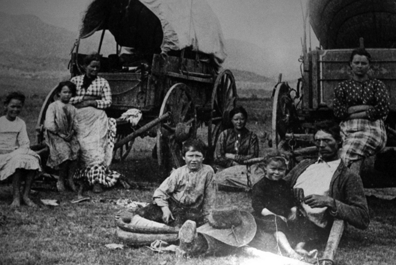 Frontier family poses in front of covered wagon; photo.