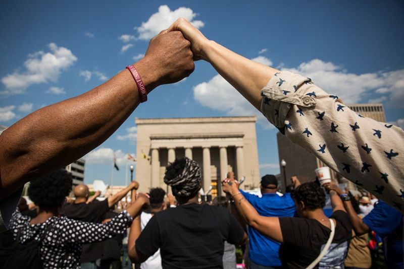 people of different races clasp hands at a rally